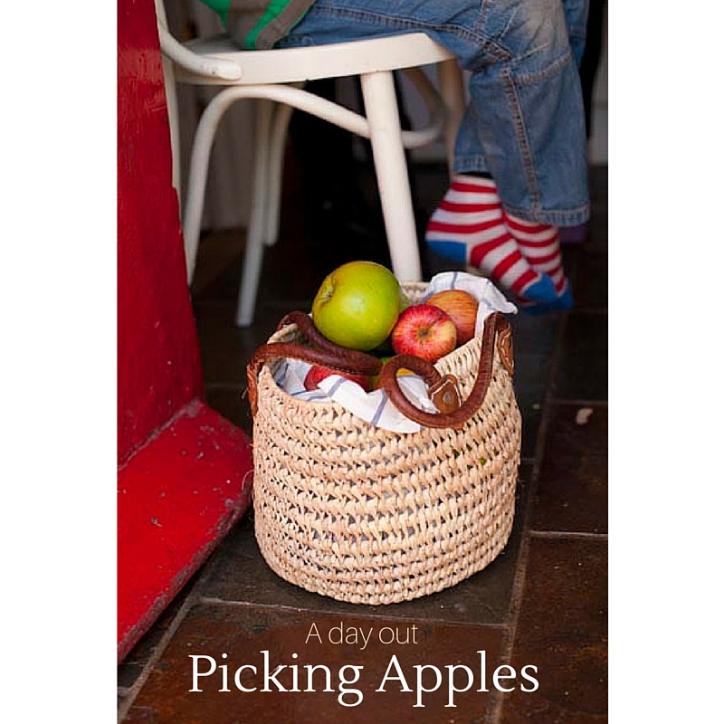 a basket of apples on a kitchen floor, childs feet just seen